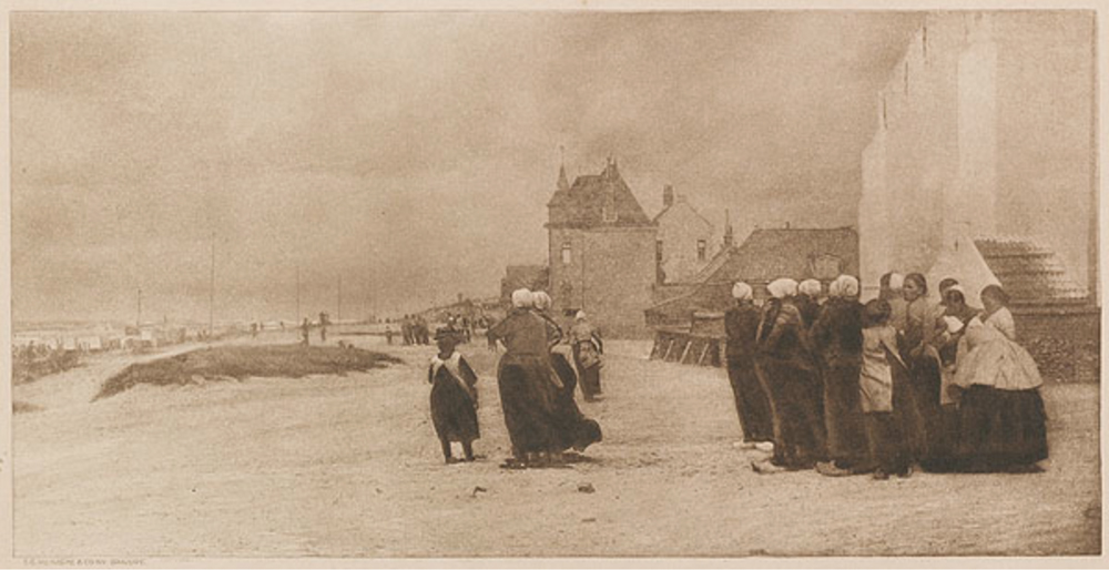 A group of women on the sore, staring out to the sea that is just out of frame on the left.