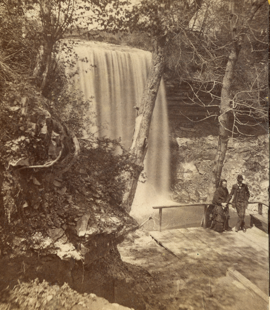 2 people on the side of the Minnehaha gorge, on a wooden platform with tall railings.