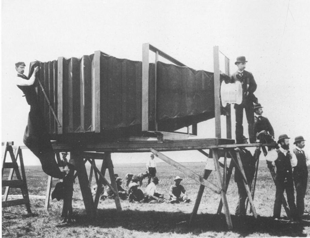 an old-tin camera with a bellows structure to distance the lens from the glass plate inside. It's on a purpose-built tower about 6 feet off the ground, and is taking a picture. The lens cover is as large as a trashcan lid.
